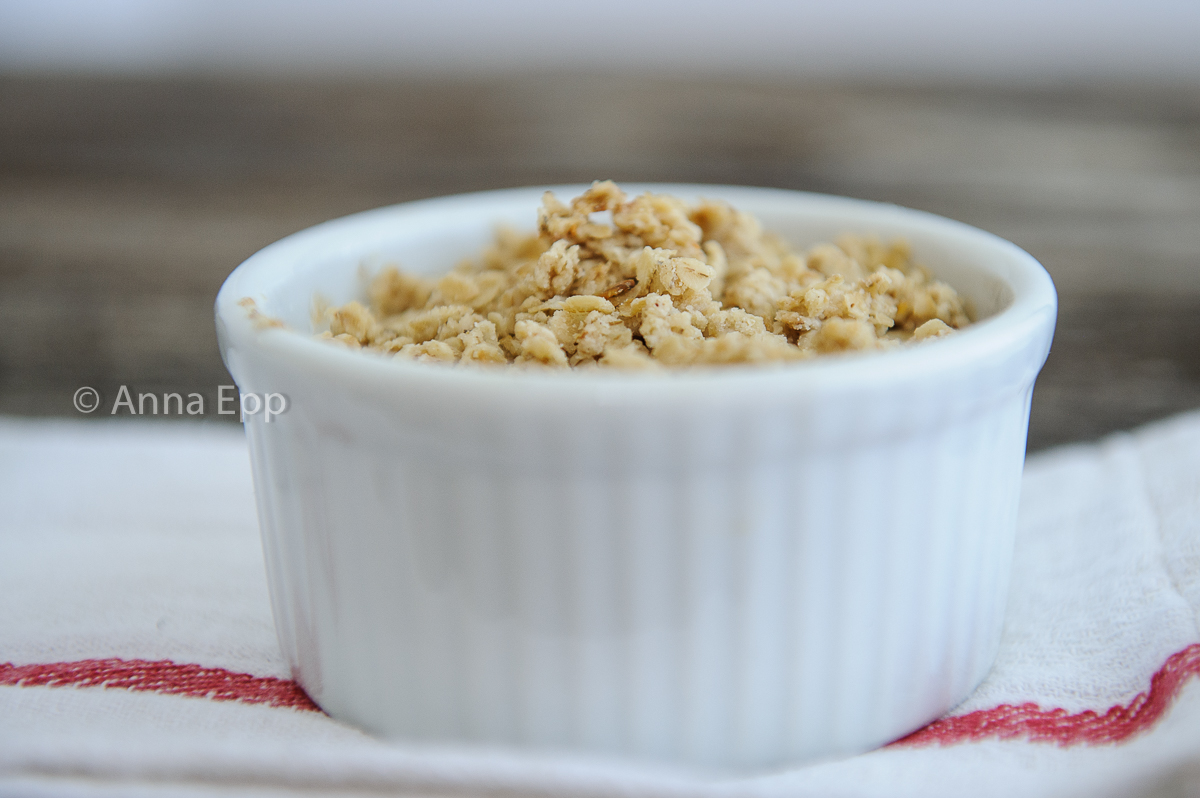 Baked Apple Crisp in a white ramkin, sitting on a white napkin with red ribbing.