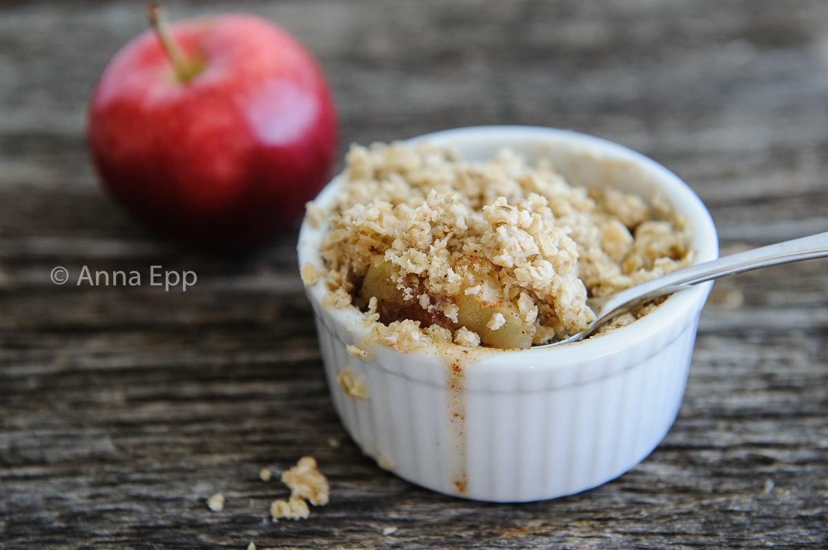 Apple crisp in a ramkin with a spoon, red apple in the background